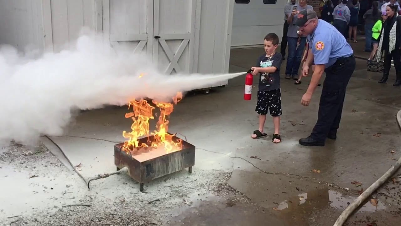 Child using a fire extinguisher on a controlled fire