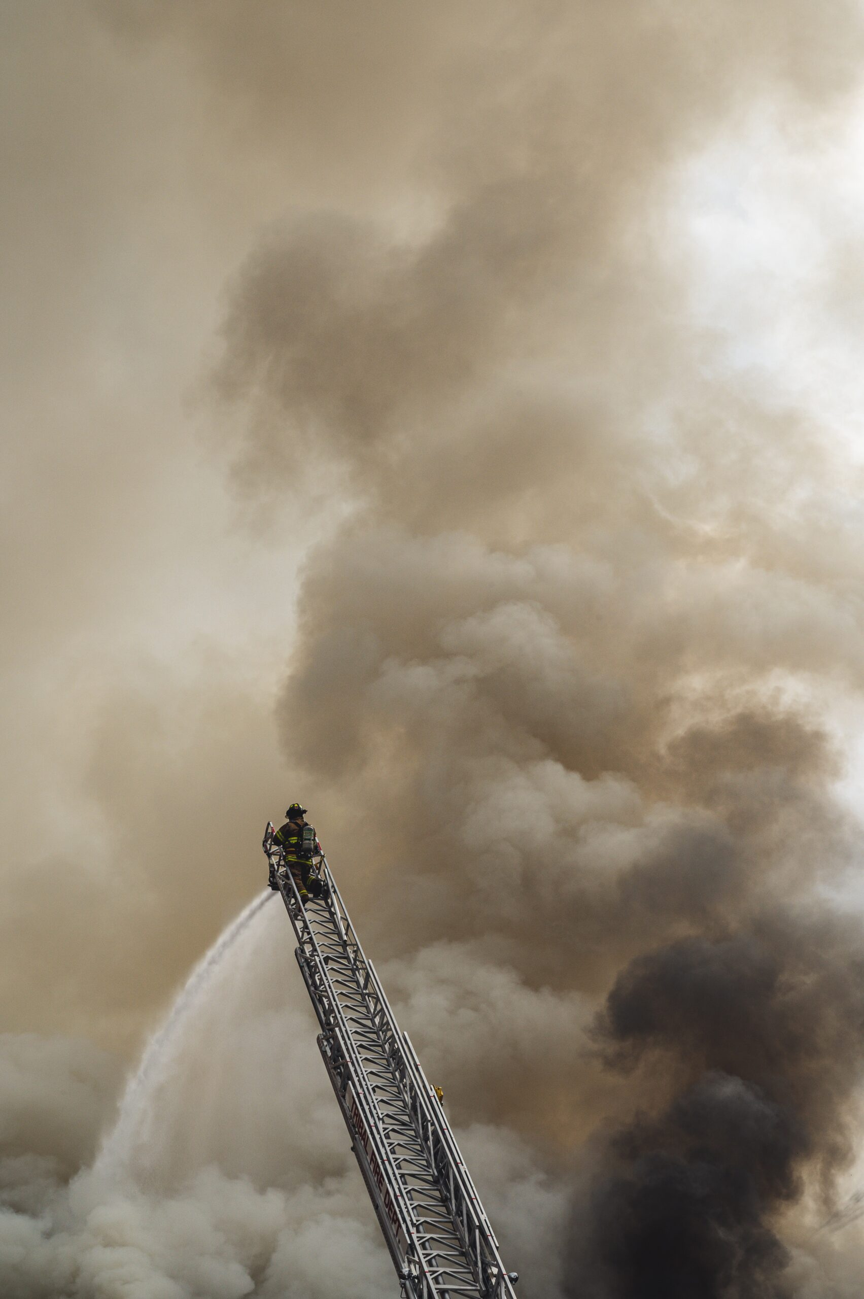 a firefighter spray water from a ladder into smoke clouds