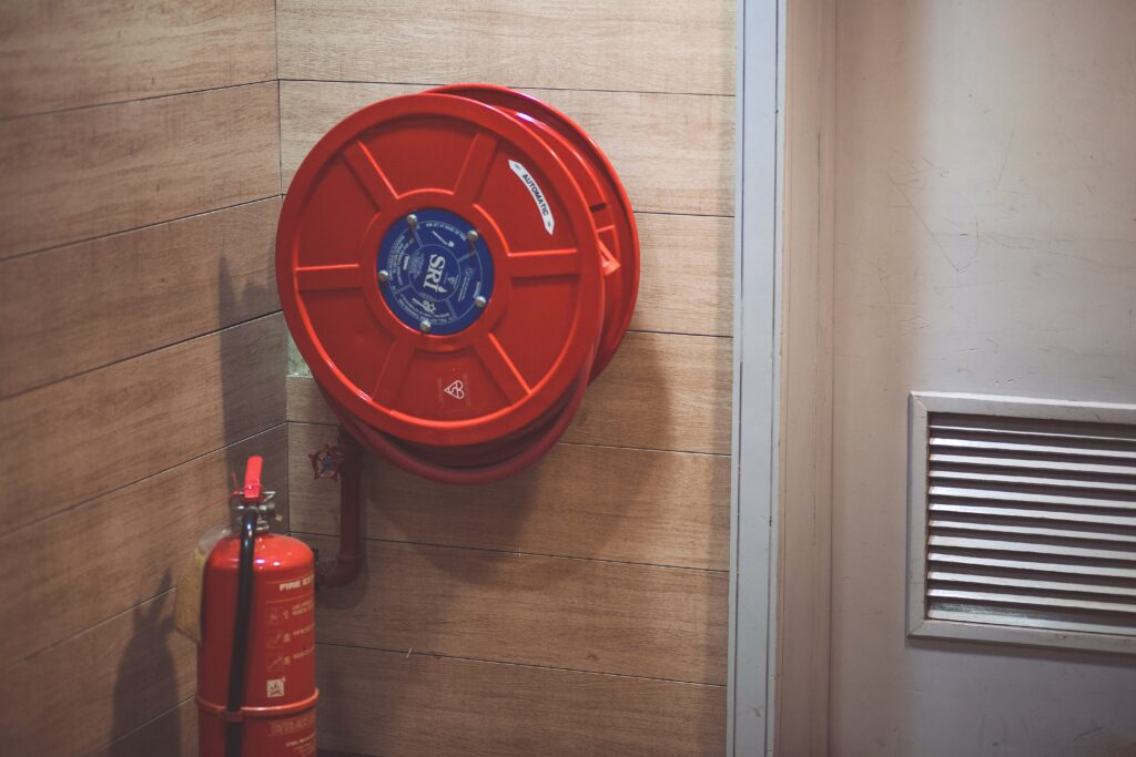 a fire extinguisher and fire hose mounted beside a door